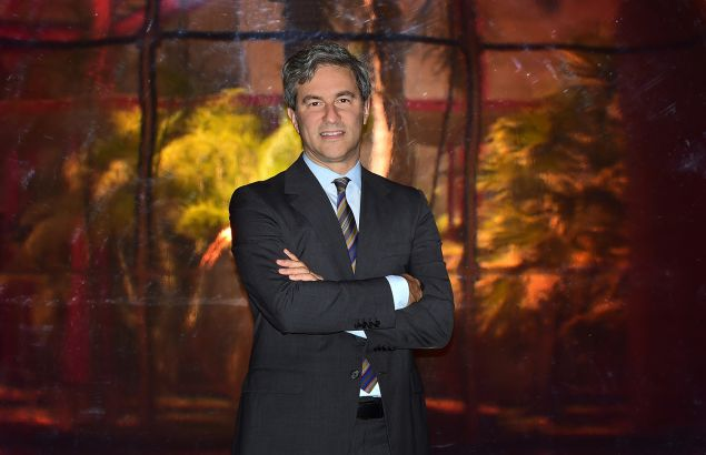 """Michael Govan, Director of the Los Angeles County Museum of Art (LACMA), poses on April 28, 2015 in Los Angeles, California, in front of 'Red Concave Circle' by DeWain Valentine on exhibit at the museum for its 50th anniversary. AFP PHOTO / FREDERIC J. BROWN """"MANDATORY MENTION OF THE ARTIST DEWAIN VALENTINE UPON PUBLICATION"""" (Photo credit should read FREDERIC J. BROWN/AFP/Getty Images)"""