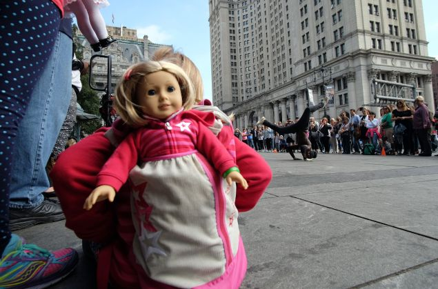 A girl with her doll peeking out of her backpack watches as a street entertainer dances during a road side show in New York on October 9, 2015. AFP PHOTO/JEWEL SAMAD (Photo credit should read JEWEL SAMAD/AFP/Getty Images)