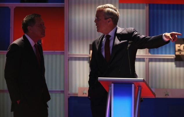 MILWAUKEE, WI - NOVEMBER 10: Republican presidential candidate Jeb Bush speaks with Ohio Gov. John Kasich during a commercial break at the Republican Presidential Debate sponsored by Fox Business and the Wall Street Journal at the Milwaukee Theatre November 10, 2015 in Milwaukee, Wisconsin. The fourth Republican debate is held in two parts, one main debate for the top eight candidates, and another for four other candidates lower in the current polls. (Photo by Scott Olson/Getty Images)