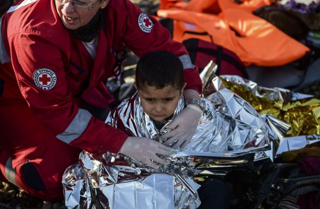 A Kurdish boy from the Syrian city of Afrin receives help after arriving on the Greek island of Lesbos along with other migrants and refugees, on November 17, 2015, after crossing the Aegean Sea from Turkey. At least eight people drowned when a boat carrying migrants from Turkey sank off the Greek island of Kos, the coastguard said on November 17, 2015. They were the latest of nearly 3,500 deaths at sea this year among people making desperate bids to flee war and poverty and to reach Europe, according to UN figures. European leaders tried to focus on joint action with Africa to tackle the migration crisis, as Slovenia became the latest EU member to act on its own by barricading its border. AFP PHOTO/BULENT KILIC (Photo credit should read BULENT KILIC/AFP/Getty Images)