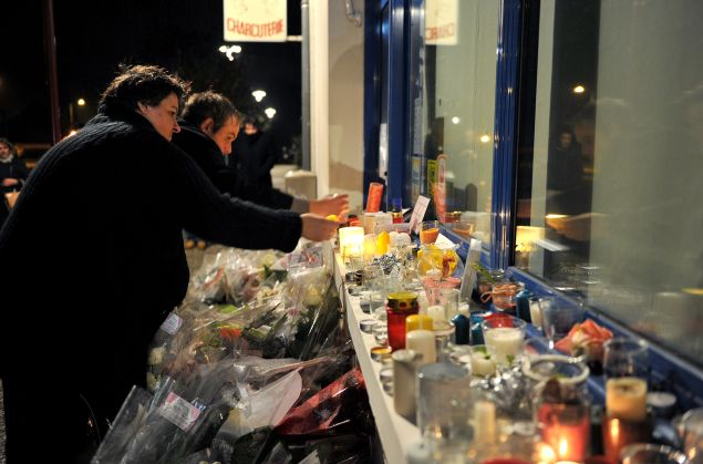 """People light candles outside the Petard Butcher Shop in Chailles, near Blois, central France, on November 17, 2015, to pay tribute to Anna and Marion Petard-Lieffrig, victims of the attacks claimed by Islamic State (IS) on November 13 in Paris. Anna Petard, 26 years old, and her sister Marion, 30 years old, were killed in the restaurant """"Le petit Cambodge"""". AFP PHOTO / GUILLAUME SOUVANT (Photo credit should read GUILLAUME SOUVANT/AFP/Getty Images)"""
