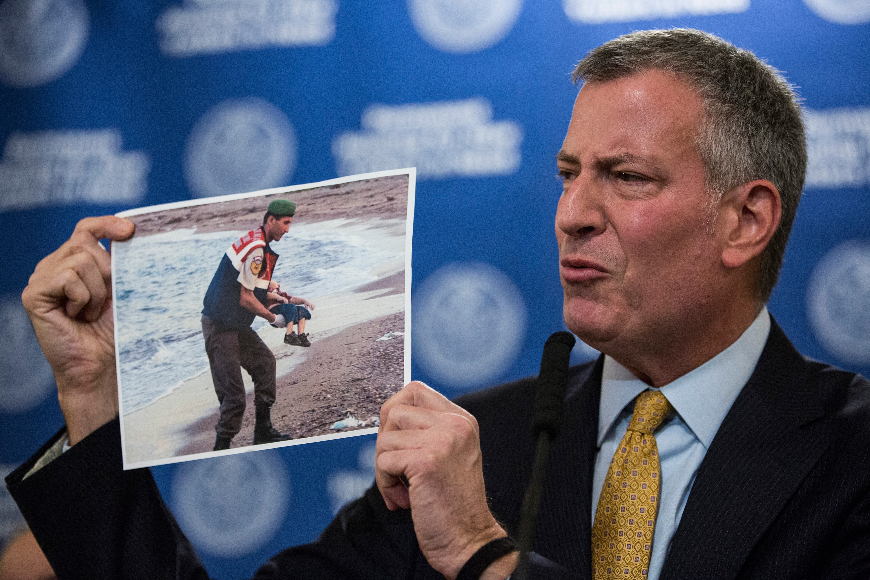 New York City Mayor Bill de Blasio holds up a photo of a the body of a dead child refugee being recovered from a beach while criticizing New Jersey Governor Chris Christie and his plan to reject refugees from the state of New Jersey during a question-and-answer period at the end a press conference announcing a new initiative for public housing for homeless people (Photo by Andrew Burton/Getty Images)