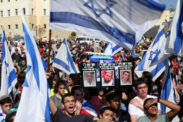Israeli students, from the Israeli settlement of Kiryat Arba in the occupied West Bank, wave their national flags and hold up pictures of Israeli victims from recent Palestinian attacks, during a protest outside Israeli Prime Minister Benjamin Netanyahu office in Jerusalem on November 22, 2015, to demand more security on West Bank roads. AFP PHOTO/GALI TIBBON (Photo credit should read GALI TIBBON/AFP/Getty Images)