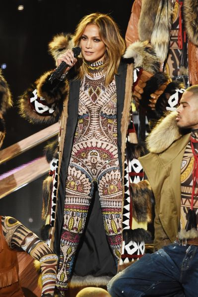 Jennifer Lopez gets the show started in a custom DSquared2 jumpsuit and coat (Photo: Getty Images).
