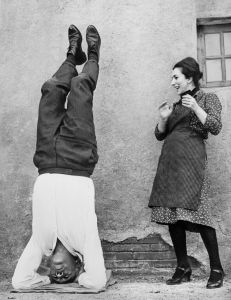 """ROME, ITALY: Italian actress Valentina Cortese smiles at US actor Anthony Quinn relaxing in a yoga position 17 December 1963 in Rome, during the shooting of """"The Visit"""" directed by Serge Miller. Born to an Irish father and Mexican mother 21 April 1915 in Chihuahua, Mexico, Anthony Quinn enjoyed a breef career as a prizefighter before entering movies in 1936. Quinn won his first Academy Award in 1952 as the brother of a Mexican revolutionary (played by Marlon Brando) in """"Viva Zapata"""". High spots include """"La Strada """" (Fellini, 1954), """"Lust for Life"""" (1956), """"The Hunchback of Notre Dame"""" (1957)... In 1962 he contributed a vibrant performance as an amoral Bedouin chieftain in David Lean's Lawrence of Arabia. Starring an earthy Greek peasant in """"Zorba the Greek"""" he won an Academy Award in 1964. Quinn died 03 June 2001 in Boston, USA. (FILM) AFP PHOTO (Photo credit should read AFP/AFP/Getty Images)"""