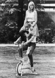English racing driver James Hunt (1947 - 1993) poses on an exercise bicycle with ex-girlfriend Jane Birbeck on his shoulders to publicise the opening of their health club 'Bodys', 10th May 1982. (Photo by Gary Stone/Central Press/Hulton Archive/Getty Images)