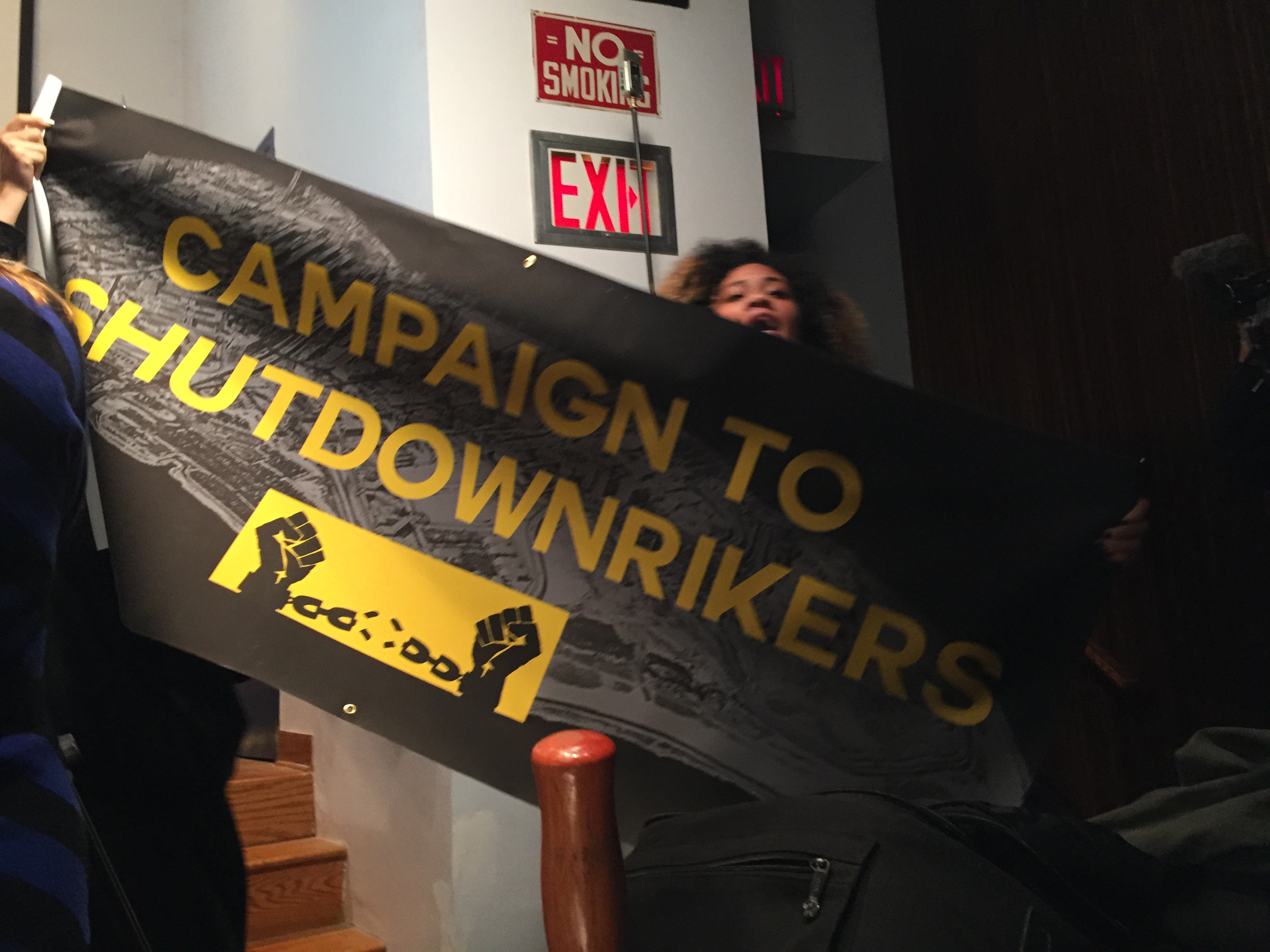 A woman holds up a banner calling for Rikers Island to be shut down. (Photo: Jillian Jorgensen for Observer)