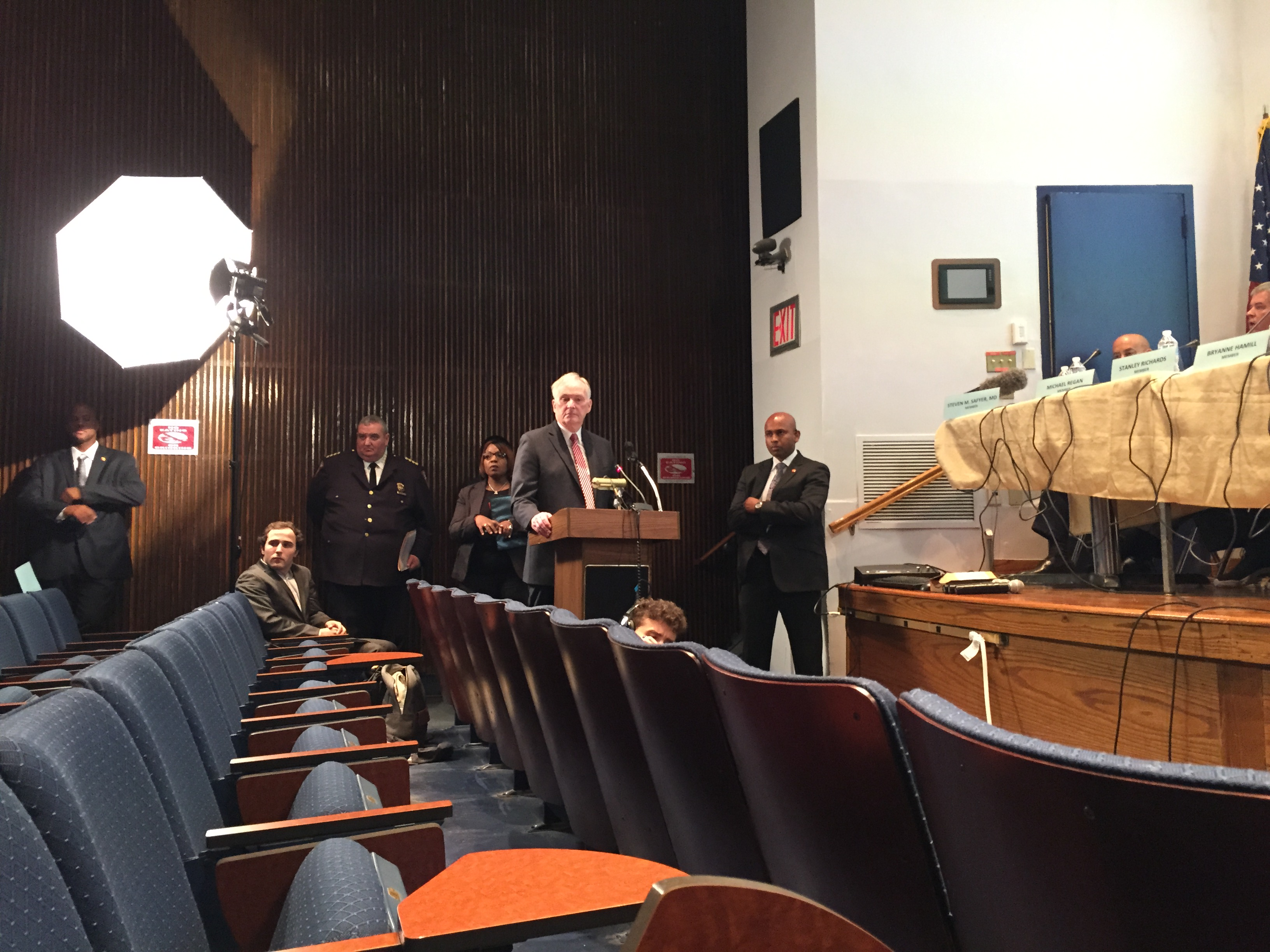 Correction Commissioner Joseph Ponte stands alone at a podium as protesters interrupt him. (Photo: Jillian Jorgensen for Observer)
