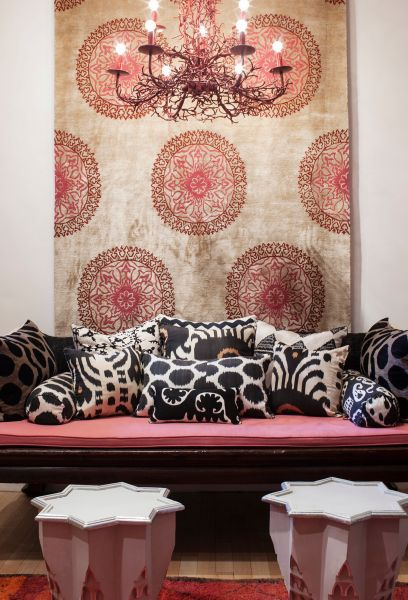 Madeline's ikat pillows on a vintage opium bed in her showroom. On the wall: Madeline's Gold Silk Gemma Tibetan Carpet (Photo: Andrea Chu for Observer).