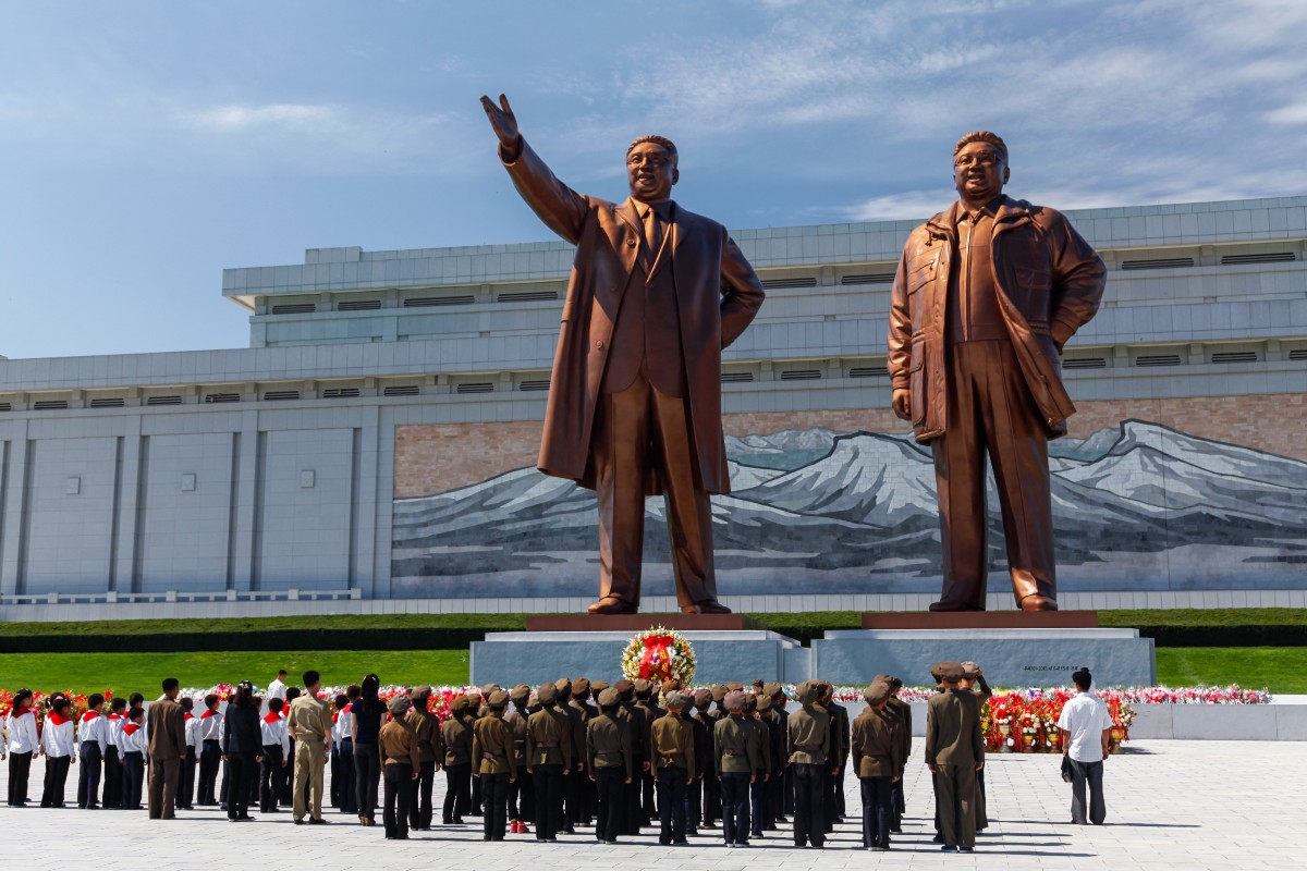 Young soldiers lining up to bow in front of massive statues of Kim Il Sung and Kim Jong Il