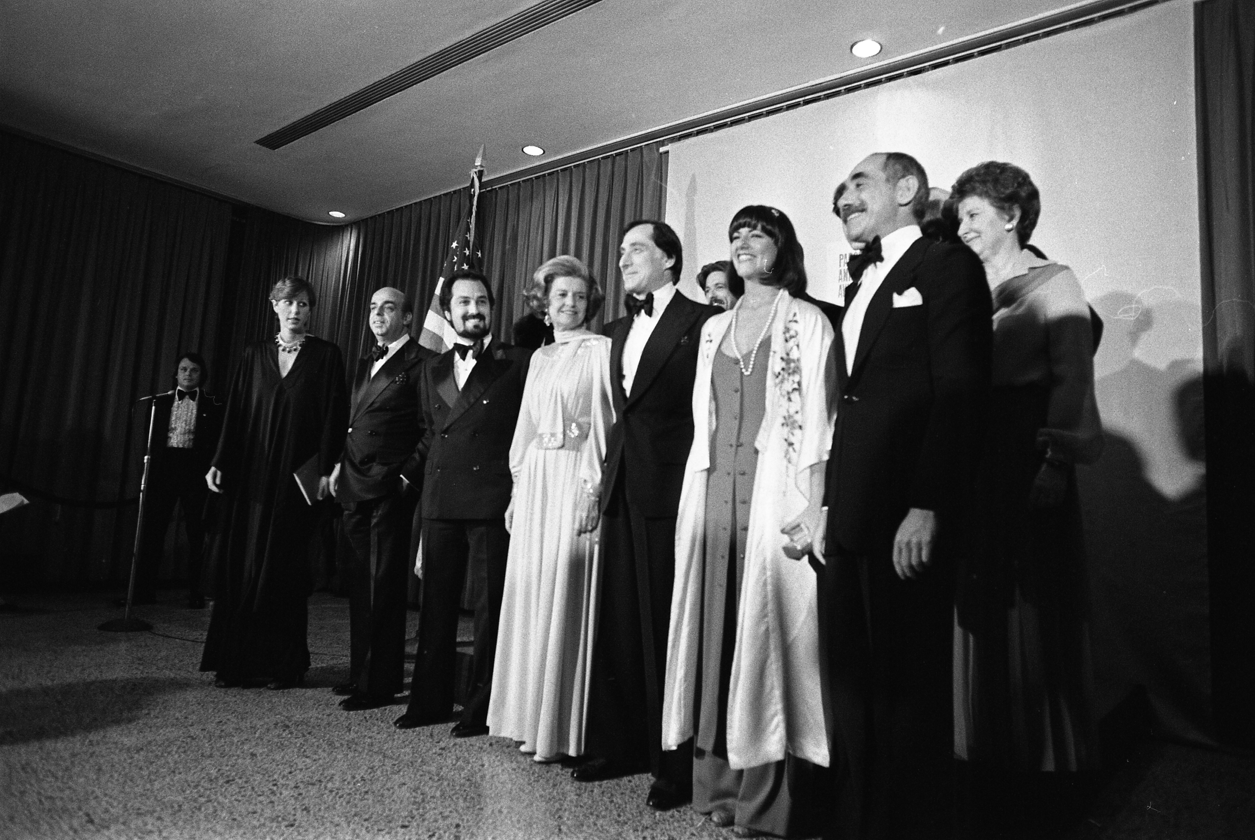 1976, March 29 – Parsons School of Design – New York, NY – Donna Karan, Donald Brooks, Albert Capraro, Betty Ford, Kasper, Kay Unger, Chester Weinberg; Liz Claiborne, Shannon Rodgers, Leo Narducci, Anthony Muto, Calvin Klein – Betty Ford standing with critics, fashion designers; formal wear – Parsons School of Design Fashion Critics Award Show and Dinner-First Lady Receves Parsons Award; Fashion Designers