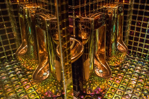 Gold colored urinals in the men's bathroom at The Robot Restaurant in Tokyo, Japan. (Photo by Chris McGrath/Getty Images).
