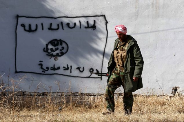 "A Kurdish fighter walks by a wall bearing a drawing of the flag of the Islamic State (IS) group in the northern Iraqi town of Sinjar, in the Nineveh Province, on November 13, 2015. Iraqi Kurdish leader Massud Barzani announced the ""liberation"" of Sinjar from the Islamic State group in an assault backed by US-led strikes that cut a key jihadist supply line with Syria. AFP PHOTO / SAFIN HAMED / AFP / SAFIN HAMED (Photo credit should read SAFIN HAMED/AFP/Getty Images)"