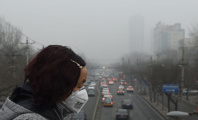 A woman wears a face mask on a heavily polluted day in Beijing on December 26, 2015. Thick smog continued a day after Beijing residents woke up to a white Christmas on December 25 with the sky obscured by thick toxic smog rather than snow. AFP PHOTO / GREG BAKER / AFP / GREG BAKER (Photo credit should read GREG BAKER/AFP/Getty Images)