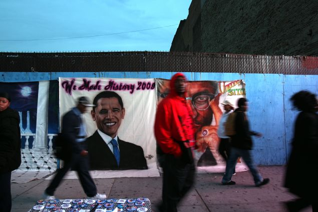 NEW YORK - NOVEMBER 04: Residents of the historically African-American neighborhood of Harlem walk by images of human rights activist Malcolm X and Democratic presidential nominee U.S. Sen. Barack Obama (D-IL) on Election Day on November 4, 2008 in New York City. After months of sometimes heated campaigning between Republican presidential nominee Sen. John McCain (R-AZ) and Obama, Americans are finally voting today for the president of the United States. (Photo by Spencer Platt/Getty Images)