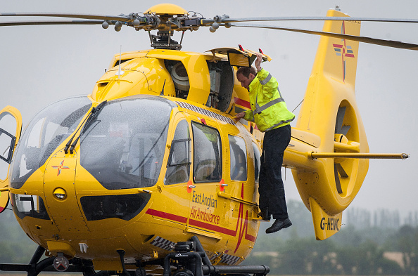 CAMBRIDGE , UNITED KINGDOM - JULY 13: Prince William, The Duke of Cambridge performs checks on his helicopter as he begins his new job with the East Anglian Air Ambulance (EAAA) at Cambridge Airport on July 13, 2015 in Cambridge, England. The former RAF search and rescue helicopter pilot will work as a co-pilot transporting patients to hospital from emergencies ranging from road accidents to heart attacks. (Photo by Stefan Rousseau WPA - Pool/Getty Images)