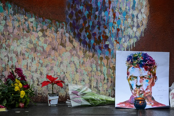 """Floral tributes are left beneath a mural of British singer David Bowie, following the announcement of Bowie's death, in Brixton, south London, on January 11, 2016. British music icon David Bowie died of cancer at the age of 69, drawing an outpouring of tributes for the innovative star famed for groundbreaking hits like """"Ziggy Stardust"""" and his theatrical shape-shifting style. AFP PHOTO / CHRIS RATCLIFFE / AFP / CHRIS RATCLIFFE (Photo credit should read CHRIS RATCLIFFE/AFP/Getty Images)"""