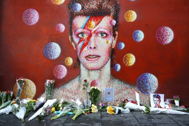 Flowers are laid beneath a mural of David Bowie. (Photo by Carl Court/Getty Images)