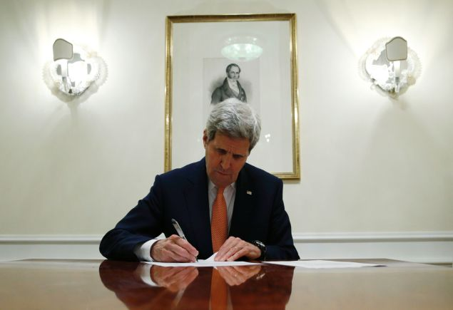 US Secretary of State John Kerry signs a series of documents during the E3/EU+3 and Iran talks in Vienna on January 16, 2016. The historic nuclear accord between Iran and major powers entered into force as the UN confirmed that Tehran has shrunk its atomic programme and as painful sanctions were lifted on the Islamic republic. / AFP / POOL / KEVIN LAMARQUE (Photo credit should read KEVIN LAMARQUE/AFP/Getty Images)