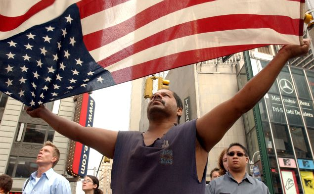 A man unfurls the American flag on the first anniversary of 9/11 (Photo: Justin Sullivan for Getty Images)