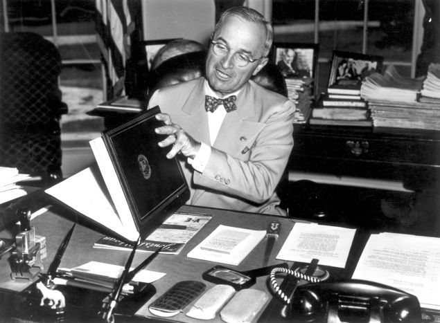 12th July 1945:  The 33rd President of the United States Harry S Truman (1884 - 1972) examining the United Nations Charter in Washington. The UN Charter was drawn up and signed by representatives of 50 countries at the UN Conference on International Organization.  (Photo by Fox Photos/Getty Images)