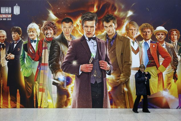A security guard walks past a giant Doctor Who poster at the 'Doctor Who 50th Celebration' event in the ExCeL centre on November 22, 2013 in London, England. The sold-out three day event in the ExCeL London convention centre celebrates 50 years of the show which has seen 11 actors play the role of Doctor Who and receives a worldwide cult following. (Photo by Oli Scarff/Getty Images)