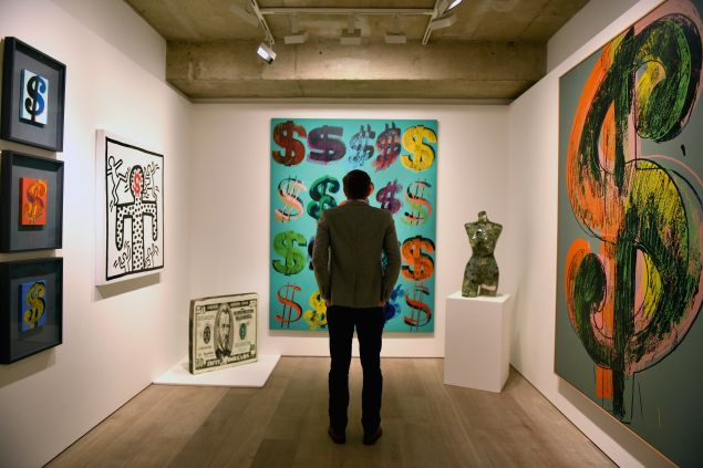 LONDON, ENGLAND - JUNE 08: A visitor studies 'Dollar Signs', 1981, by Andy Warhol which has an estimated value of £4.5-6.5 million and is going on show at Sotheby's on June 8, 2015 in London, England. The work is a centrepiece of an exhibition of 21 pieces inspired by the US Dollar which are estimated to have a total value of £50 million and will go under offer by the auction house on 1st and 2nd July 2015. (Photo by Mary Turner/Getty Images)