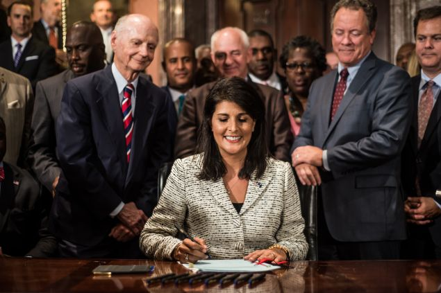 COLUMBIA, SC - JULY 9: South Carolina Governor Nikki Haley receives applause after signing a bill to remove the Confederate battle flag from the state house grounds July 9, 2015 in Columbia, South Carolina. Debate on the flag was reignited three weeks ago after the mass murder at Emanuel AME Church in Charleston, South Carolina. (Photo by Sean Rayford/Getty Images)
