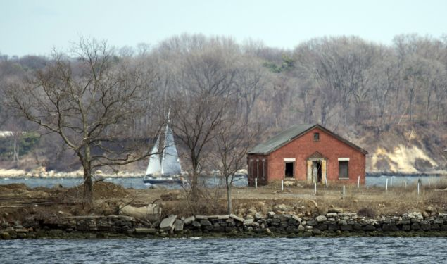 A sailboat passes behind an abandoned building on Hart Island on April 5, 2014 in New York. Each white plastic pipe near the building marks an infant mass gravesite, one plastic pipe per 1,000 babies. Hart Island, occupying 101 acres in the Long Island Sound on the eastern edge of the Bronx in New York, contains the largest cemetery in the US. One million bodies of still born babies, the poor, the unidentified and the unclaimed are buried by prison labor in common graves. It is run by the department of corrections, and access is nearly impossible. AFP PHOTO/Don Emmert (Photo credit should read DON EMMERT/AFP/Getty Images)