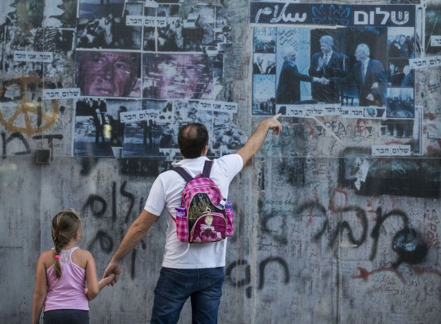An Israeli father shows to his daughter a 20-year-old picture of late Israeli prime minister Yitzhak Rabin (R) shaking hands with late Jordanian King Hussein (L) while former US president Bill Clinton applauds, on October 24, 2015 at a memorial at the place where Rabin was assassinated in the Israeli Mediterranean city of Tel Aviv in 1995 at the hands of a Jewish extremist opposed to peace with the Palestinians. Rabin was shot after giving a speech to tens of thousands of peace demonstrators in Tel Aviv. His killer, Yigal Amir, was a rightwing extremist opposed to the Oslo peace accords with the Palestinians, for which Rabin won the 1994 Nobel peace prize. AFP PHOTO / JACK GUEZ (Photo credit should read JACK GUEZ/AFP/Getty Images)