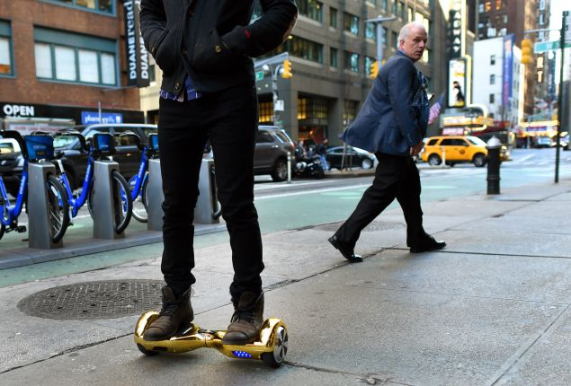 """Whizboard Store manager 'Mor Loud' demonstrates the Hoverboard on Broadway in Times Square in New York on December 15, 2015. The hot item on many holiday lists will help you zip around town, the shopping mall and from one end of the workplace to another.These so-called """"hoverboards"""" or self-balancing electric scooters, are surging in popularity in the first season where they have been available at relatively affordable prices -- as low as $300 for some models. AFP PHOTO / TIMOTHY A. CLARY / AFP / TIMOTHY A. CLARY (Photo: Timothy A. Clary/Getty Images)"""
