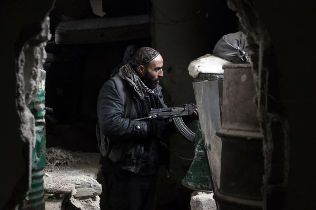 A fighter from the Jaish al-Islam (Islam Army), the foremost rebel group in Damascus province who fiercely opposed to both the regime and the Islamic State group, guards a position on the front line in Jobar, on the eastern edge of the Syrian capital on January 4, 2016. Jaish al-Islam has fought off both government forces and IS group jihadists in its Eastern Ghouta bastion, east of the capital. AFP PHOTO / AMER ALMOHIBANY / AFP / AMER ALMOHIBANY (Photo credit should read AMER ALMOHIBANY/AFP/Getty Images)