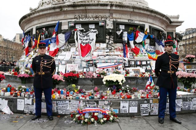 Republican guards stand beside a wreath of flowers placed by Paris' mayor and the French president at the foot of the Statue of Marianne during a remembrance rally after attacks on the Charlie Hebdo newspaper one year ago. (Photo: YOAN VALAT/AFP/Getty Images)