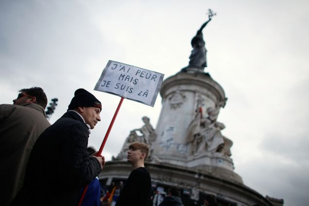 """TOPSHOT - A man holding a placard reading """"I am afraid but I am here"""" during a gathering on Place de la Republique (Republic square) on January 10, 2016 in Paris, as the city marks a year since 1.6 million people thronged the French capital in a show of unity after attacks on the Charlie Hebdo newspaper and a Jewish supermarket. Just as it was last year, the vast Place de la Republique is the focus of gatherings as people reiterate their support for freedom of expression and remember the other victims of what would become a year of jihadist outrages in France, culminating in the November 13 coordinated shootings and suicide bombings that killed 130 people and were claimed by the Islamic State (IS) group. AFP PHOTO / THOMAS SAMSON / AFP / THOMAS SAMSON (Photo credit should read THOMAS SAMSON/AFP/Getty Images)"""