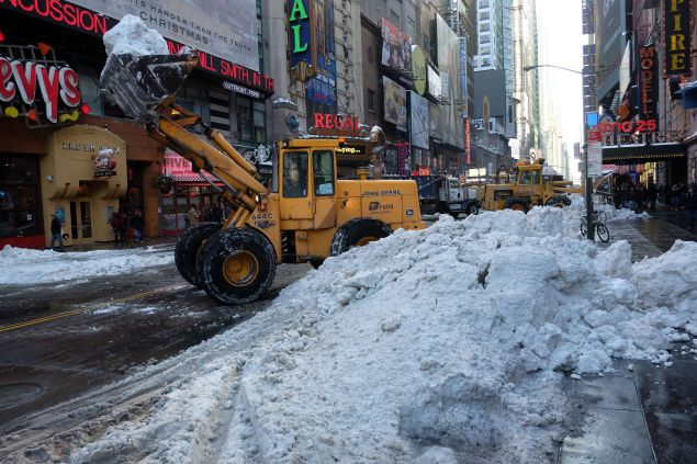 Department of Sanitation workers use bulldozers to clean pile of snow from the street in New York on January 25, 2016. The eastern US emerged wearily from a massive blizzard that dumped huge amounts of snow and killed at least 25 people, but Washington was still reeling, with government offices and schools to remain closed on Monday. / AFP / JEWEL SAMAD (Photo credit should read JEWEL SAMAD/AFP/Getty Images)
