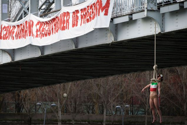 A FEMEN activist hangs from a mock noose during a protest in Paris against the visit of the Iranian president. (Photo: Joel Saget/AFP/Getty Images)
