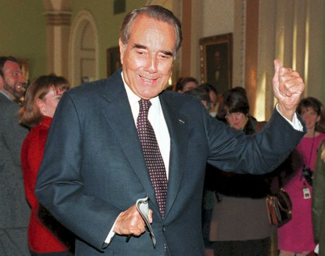 WASHINGTON, DC - DECEMBER 1:  Sen. Robert Dole (R-KS), the expected Senate majority leader, signals to current Senate Majority Leader George Mitchell (D-ME) that it is his turn to talk to reporters, 01 December 1994, in the halls of the Capitol Building in Washington. Dole had just met with Treasury Secretary Lloyd Bentsen about the GATT agreement.  (Photo credit should read ROBERT GIROUX/AFP/Getty Images)
