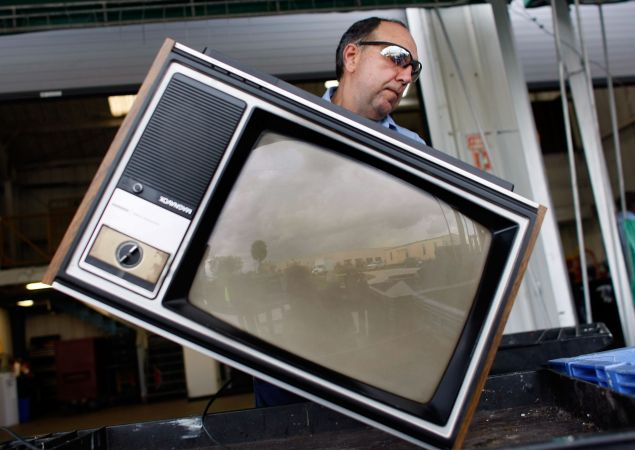 POMPANO BEACH, FL - JUNE 05: Jim Salem carries a discarded analog television set to a bin at the Broward County Waste & Recycling Services Solid Waste center on June 5, 2009 in Pompano Beach, Florida. As America switches to a digital signal on June 12th many are throwing out their old television sets. The switch to the digital television signal makes old analog televisions obsolete unless a converter box has been purchased. For the last 70 plus years people have watched television on analog. (Photo by Joe Raedle/Getty Images)