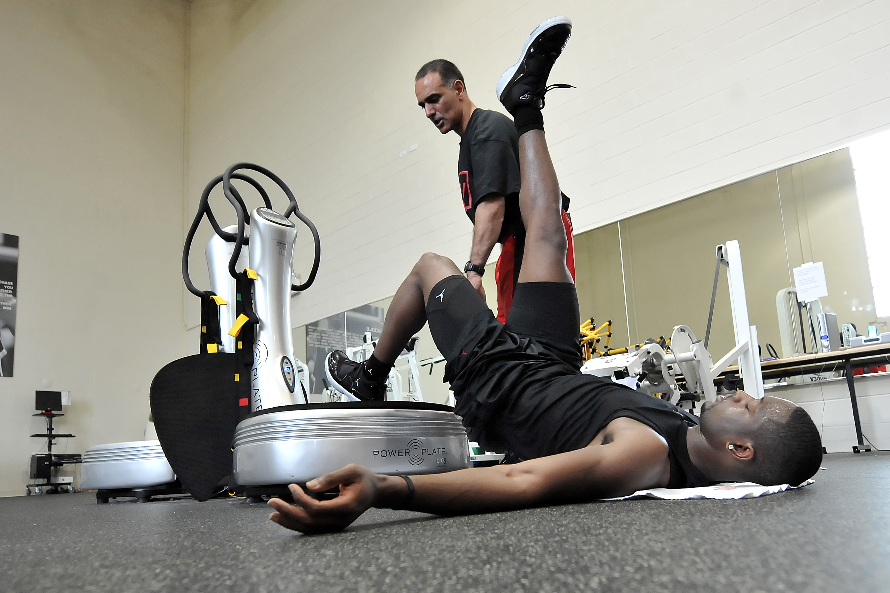 CHICAGO - SEPTEMBER 8: Dwyane Wade (R) of the Miami Heat uses a Power Plate machine help from Tim Grover, sports performance enhancement specialist and ATTACK Athletics owner, during his workout on September 8, 2009 at ATTACK Athletics in Chicago, Illinois. NOTE TO USER: User expressly acknowledges and agrees that, by downloading and/or using this photograph, user is consenting to the terms and conditions of the Getty Images License Agreement. Mandatory Copyright Notice: Copyright 2009 NBAE (Photo by Randy Belice/NBAE via Getty Images)