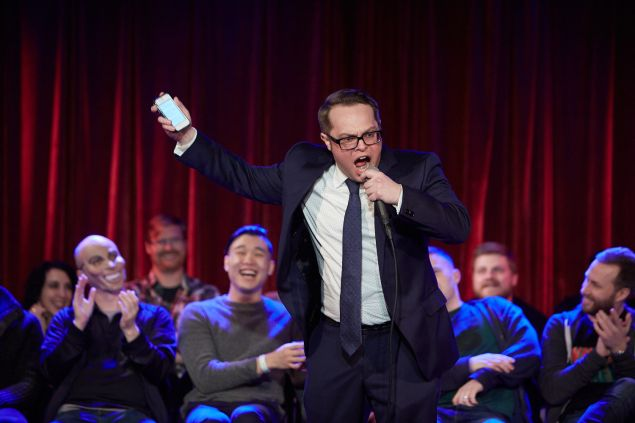 Fifty First Jokes, hosted by comic John F. O'Donnell, at The Bell House in Brooklyn, January 2nd, 2016. John F. O'Donnell during his opening monologue, with the first round of 25 comics on stage behind him. PHOTO: Harry Zernike for Observer