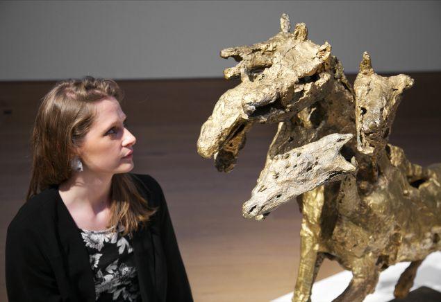 A woman poses with French sculptor Germaine Richier's masterpiece Le cheval à six têtes, grand, (1954-1956). (Photo: Bonhams)