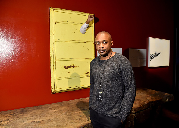 Artist Hank Willis Thomas poses next to his piece at Art For Social Justice, Usher Raymond IV, Daniel Arhsam and TIDAL debut Chains at Urban Zen on January 29, 2016 in New York City. (Photo by Michael Loccisano/Getty Images for Tidal)
