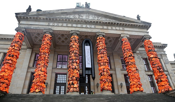 BERLIN, GERMANY - FEBRUARY 14: An art installation by Chinese artist Ai Weiwei showcases thousands of used life vests by refugees from the Greek island of Lesbos, on February 14, 2016 in Berlin, Germany. The orange vests are wrapped around the pillars of the city's Konzerthaus to highlight the plight of refugees trying to reach Europe.