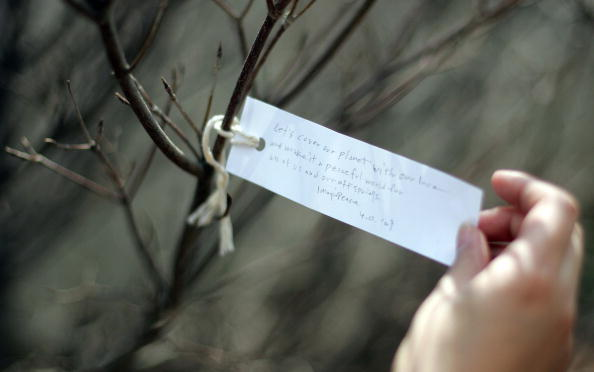 """Washington, UNITED STATES: Japanese artist Yoko Ono, widow of Beatles member John Lennon, dedicates the """"Wish Tree for Washington, DC"""" with the first wish: """"Let's cover our planet with our love and make it a peaceful world for all of us and our offsprings"""" 02 April 2007 at the Hirshorn Museum's Sculpture Garden as part of """"Yoko Ono: Imagine Peace"""" in Washington, DC. The Wish Tree series, which Ono began in the 1990s, encourages the public to become participants in the art-making process by inviting visitors to write wishes on paper and tie them to the tree. AFP PHOTO/Tim SLOAN"""