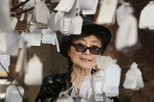 LIVERPOOL, UNITED KINGDOM - APRIL 04: Yoko Ono poses next to 'The Wish Tree', one of her art installations at The Bluecoat Display Centre on April, 2008 in Liverpool, England. The Wish Tree invites viewers to write their wishes on labels that are then fixed to the branches. Yoko Ono returned to perform and display her art at The Bluecoat 40 years after she first exhibited there in 1967 to celebrate the re-opening of the UK's oldest arts centre after a GBP 12.5 million refurbishment.