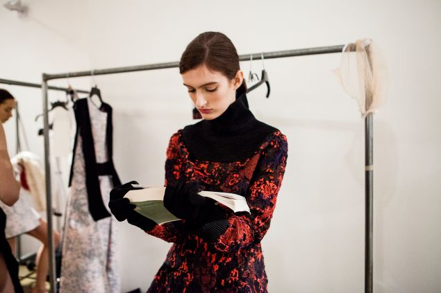 A model catches up on her reading backstage