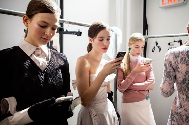 Models texting in their Gelinas creations
