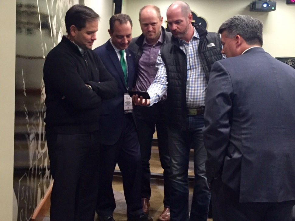 Campaign Manager Terry Sullivan (r) holds smartphone as he shows a Rubio campaign spot to, from left, the candidate, RNC Chairman Reince Priebus and Todd Harris, the Rubio campaign's media guy. (Twitter)