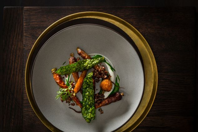 Roasted carrots over a yogurt gel and kale puree with red quinoa, chives and shallots and garnished with kale chips and green carrot tops prepared by Executive Chef/Owner Daniel Humm of NoMad Restaurant, NYC.