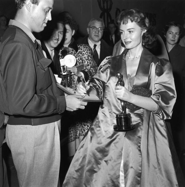 American actor Donna Reed (1921 - 1986) signs an autograph while holding her Oscar trophy at the Academy Awards, Los Angeles, California, March 25, 1954. =